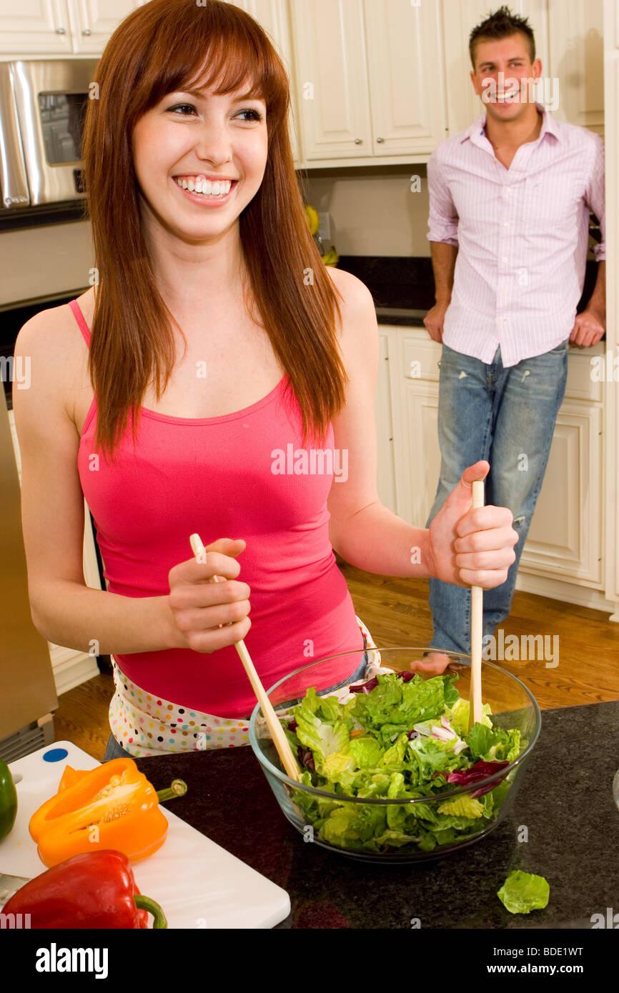 Matura in cucina facendo una insalata. Foto Stock