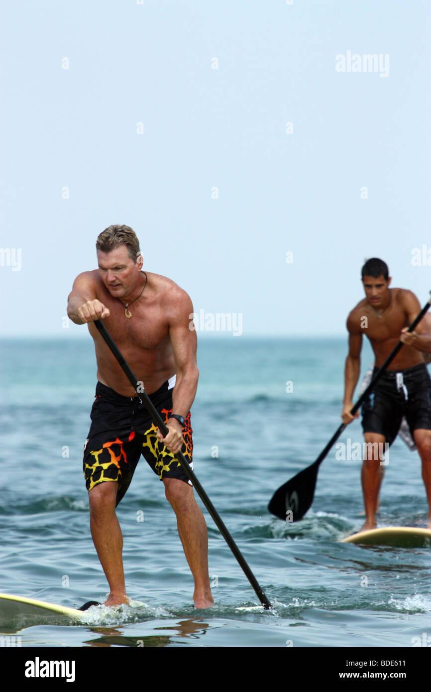 Gli uomini a competere in gara paddleboard Immagini Stock