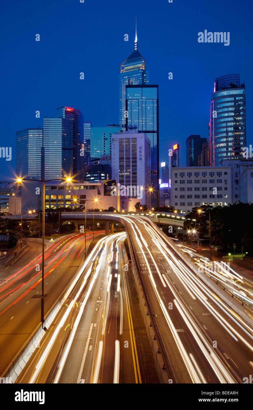 Un edificio alto e sentieri per auto a notte nel centro di Hong Kong, Cina. Immagini Stock