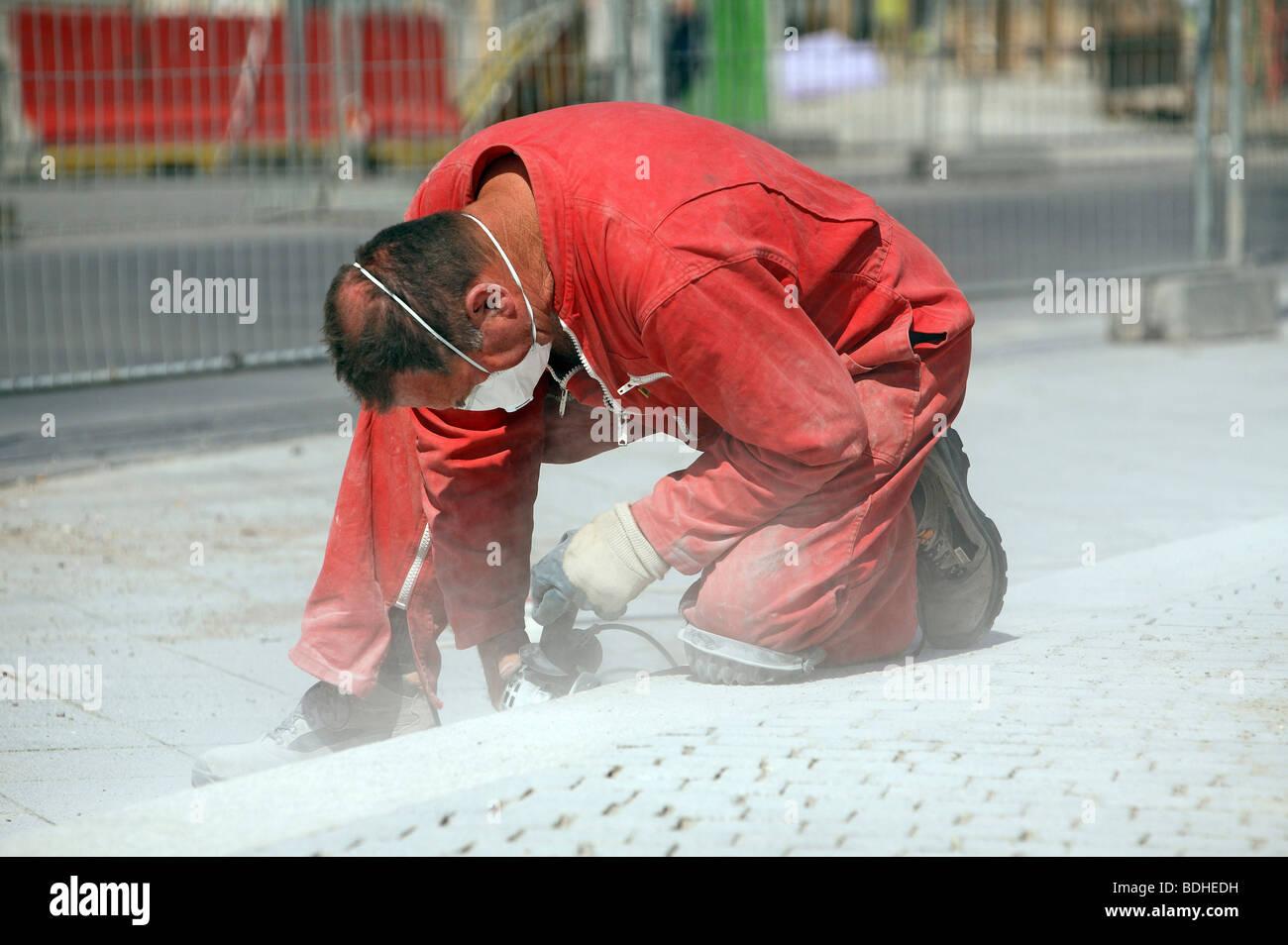 Colletto blu lavoratore il taglio di piastrelle, Francia Immagini Stock