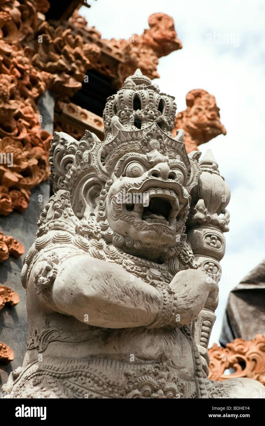 Indonesia Bali Kuta, Jalan Pantai, scolpiti nella pietra divinità Indù al di fuori del piccolo tempio Immagini Stock