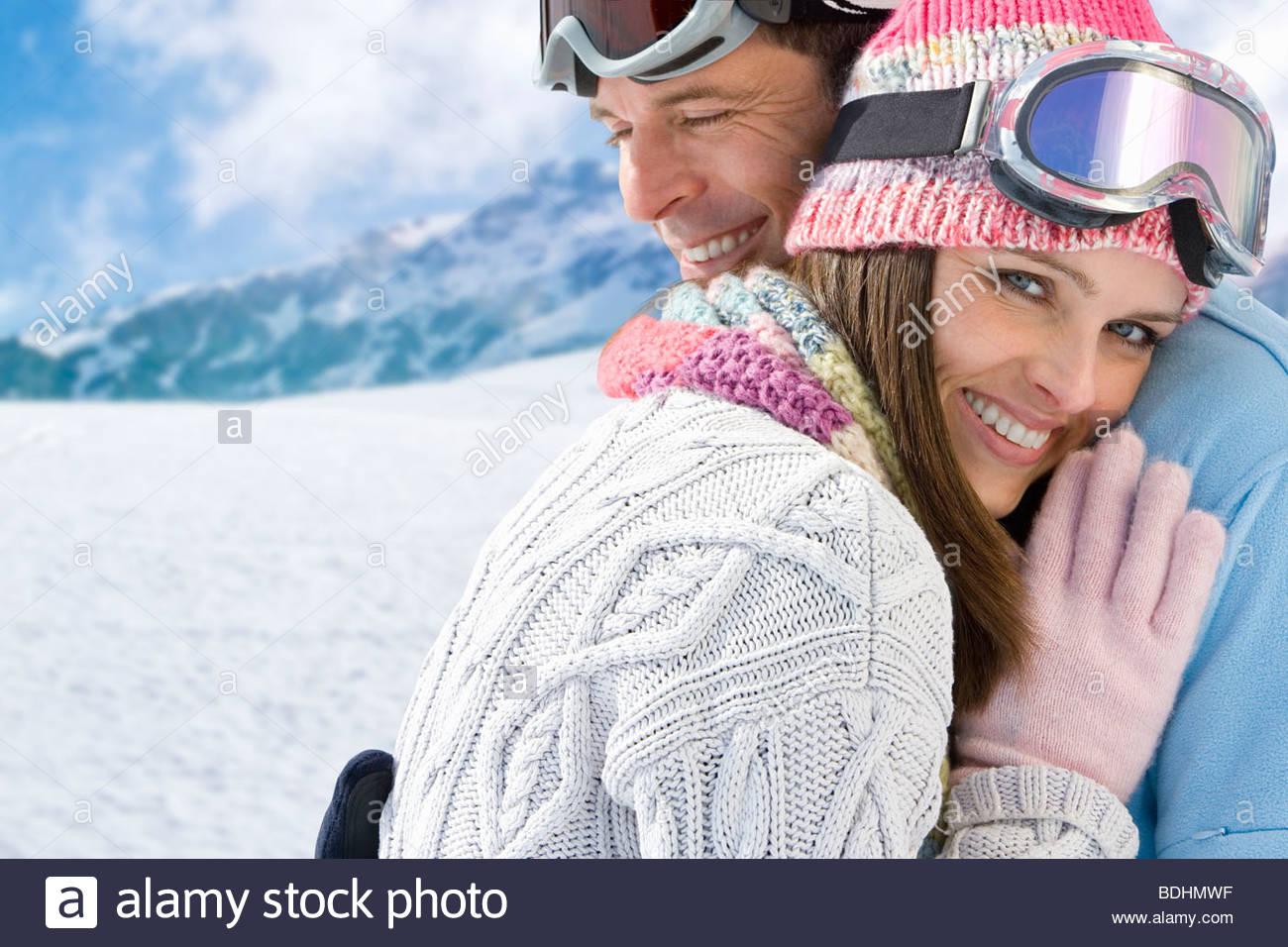 Coppia sorridente in ski-usura costeggiata sulla montagna Immagini Stock