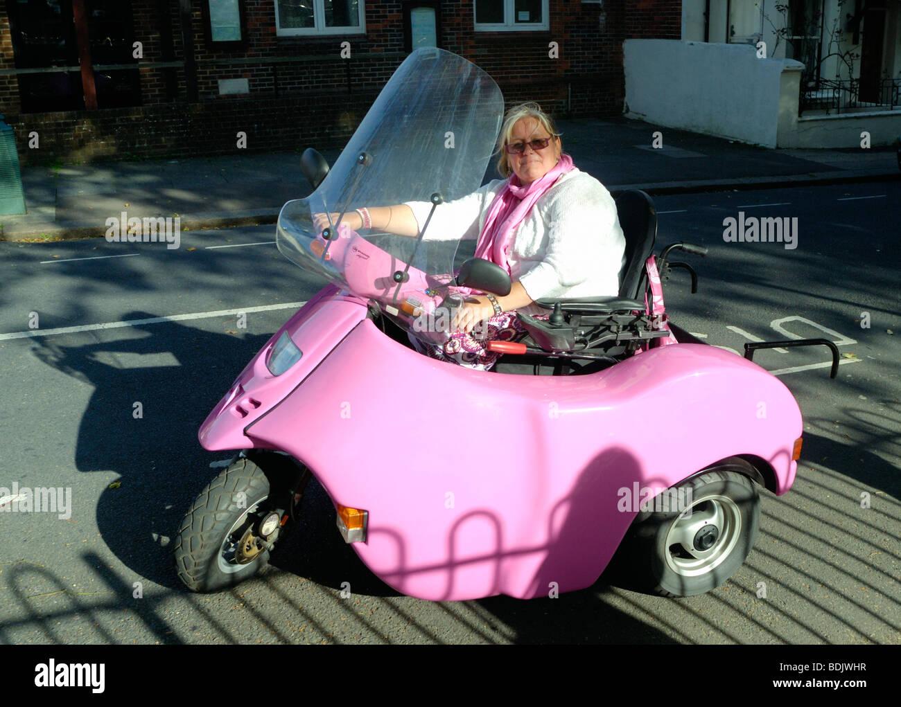 Una signora alla guida di una disabilità rosa scooter Immagini Stock