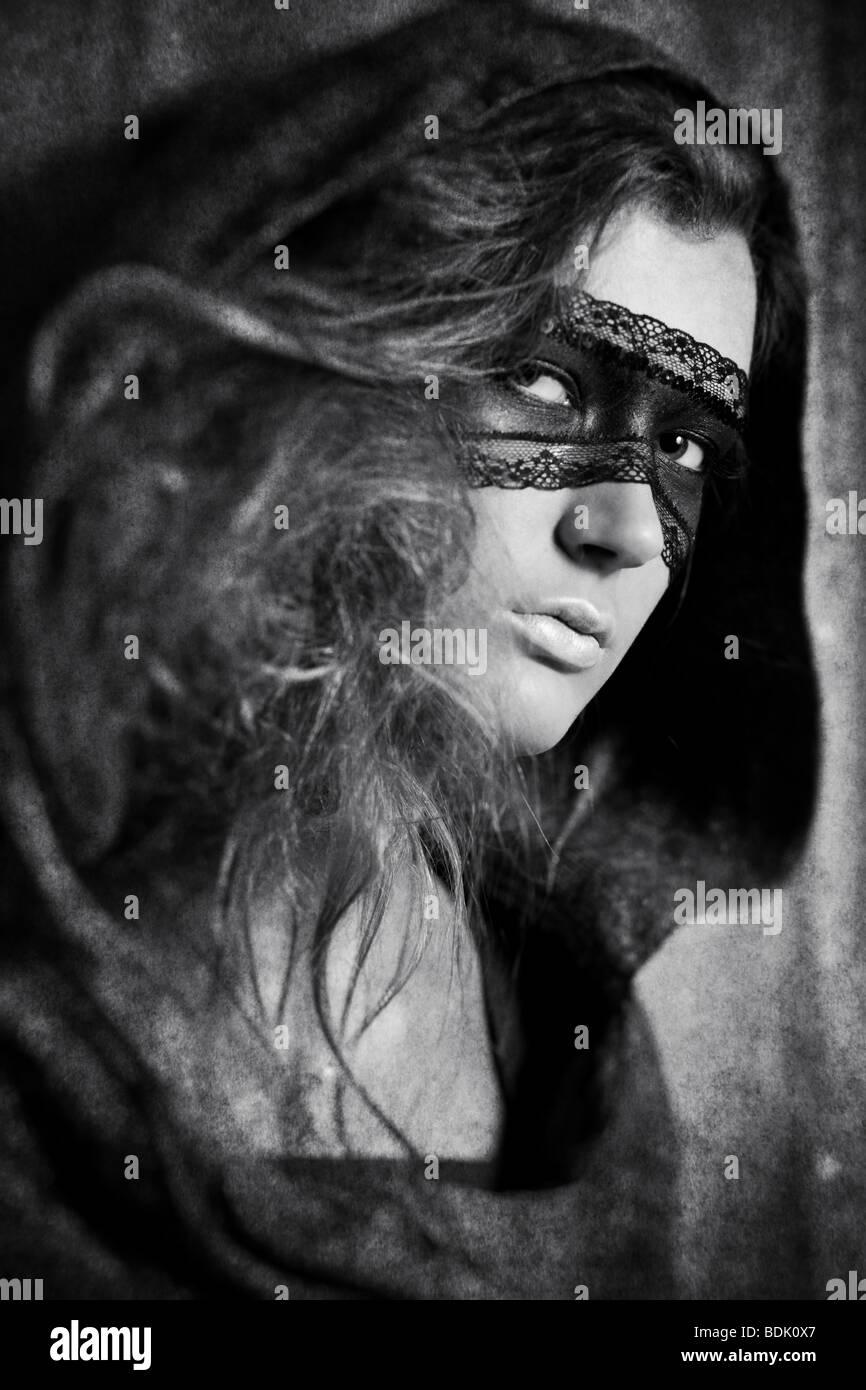 Giovane donna con maschera. Bianco e nero concetto con effetto invecchiato. Immagini Stock