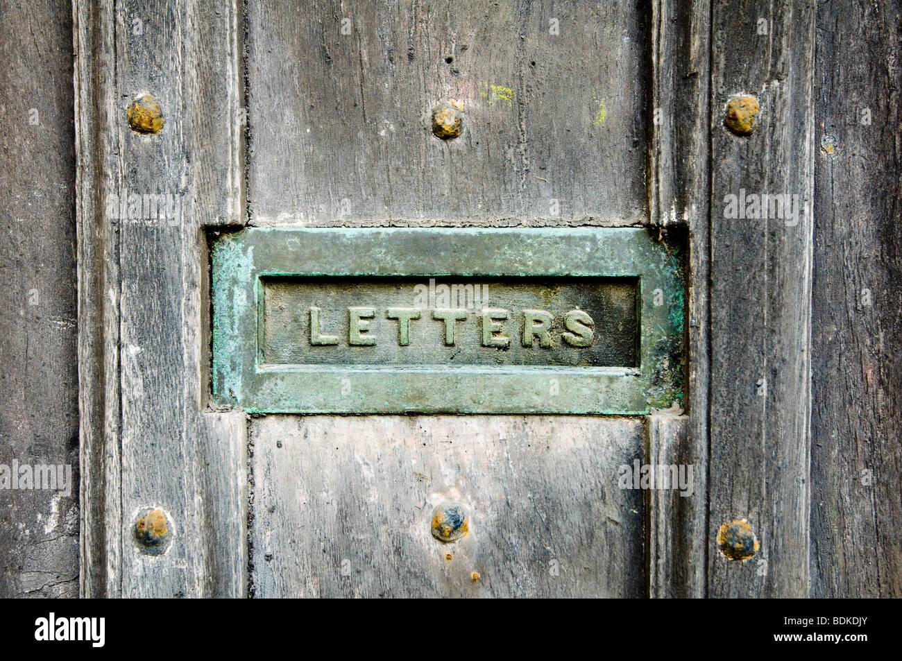 Un letter box, con una patina verdigris, inset in un vecchio e stagionato porta in legno di quercia, con chiodi Immagini Stock