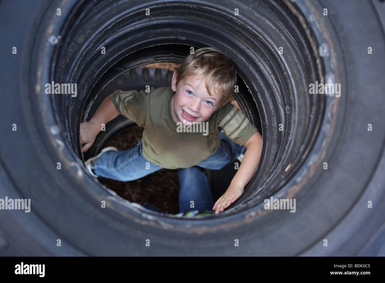 Ragazzo giovane nei pneumatici in posizione di parcheggio Immagini Stock