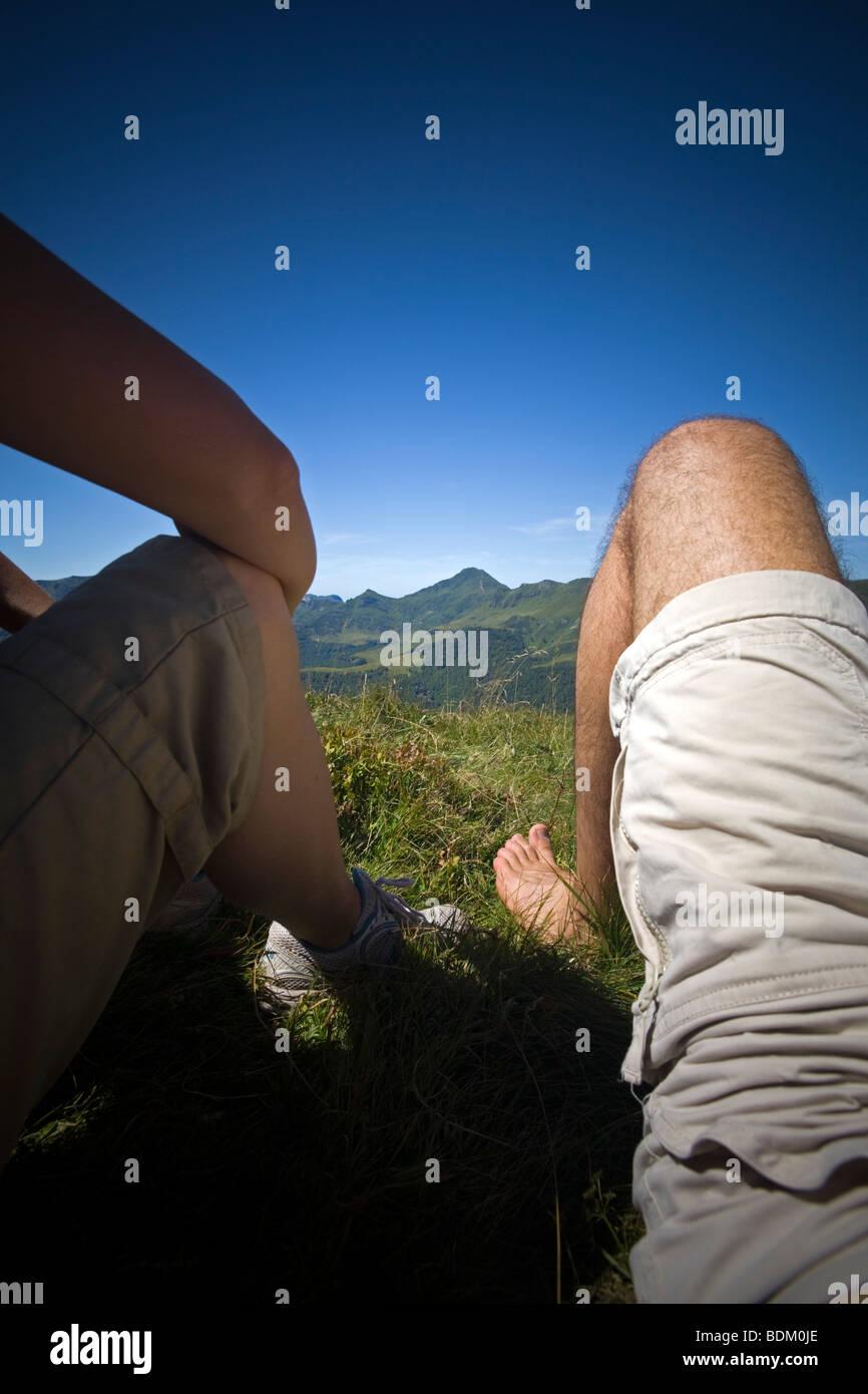 Una pausa per un paio di escursionisti di fronte al Puy Mary (Francia). Pausa pour un giovane de randonneurs devant Immagini Stock