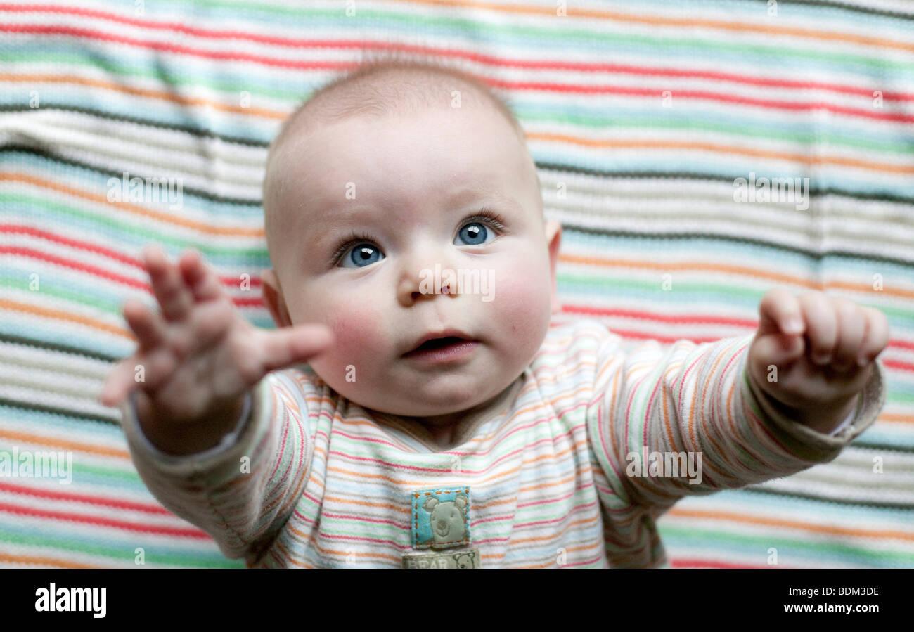 Un bambino alza le braccia a sua madre per essere prelevati. Foto Stock