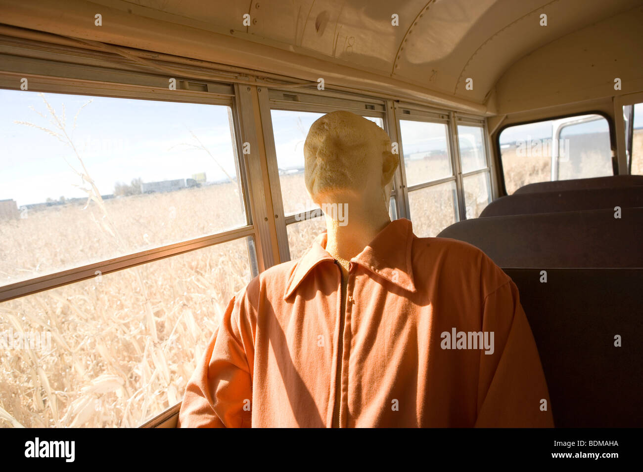 Manichino vestito di prigioniero di abbigliamento, equitazione in un bus di scuola, campo abbandonato, mais, agriturismo, Immagini Stock