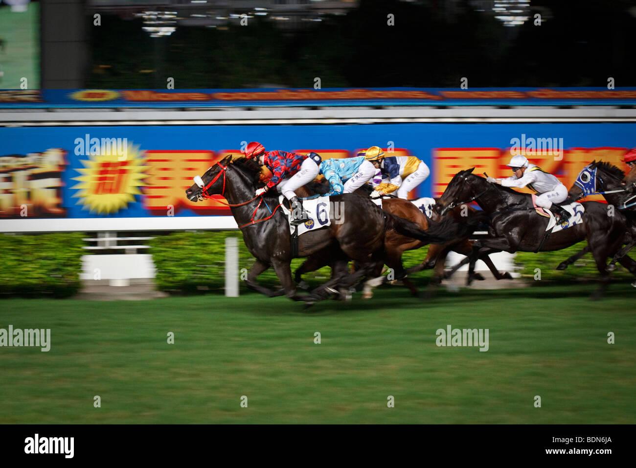 Un galoppo finale alla fine in una notte horse racing event a Happy Valley Race Course a Hong Kong. Immagini Stock