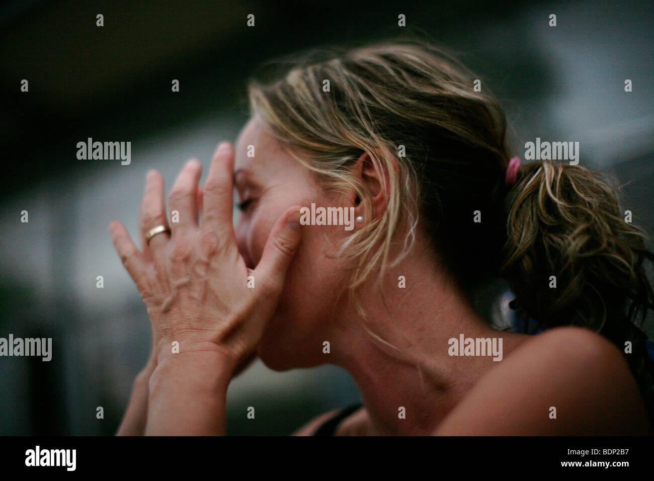 Vista laterale della giovane donna che copre il volto Immagini Stock
