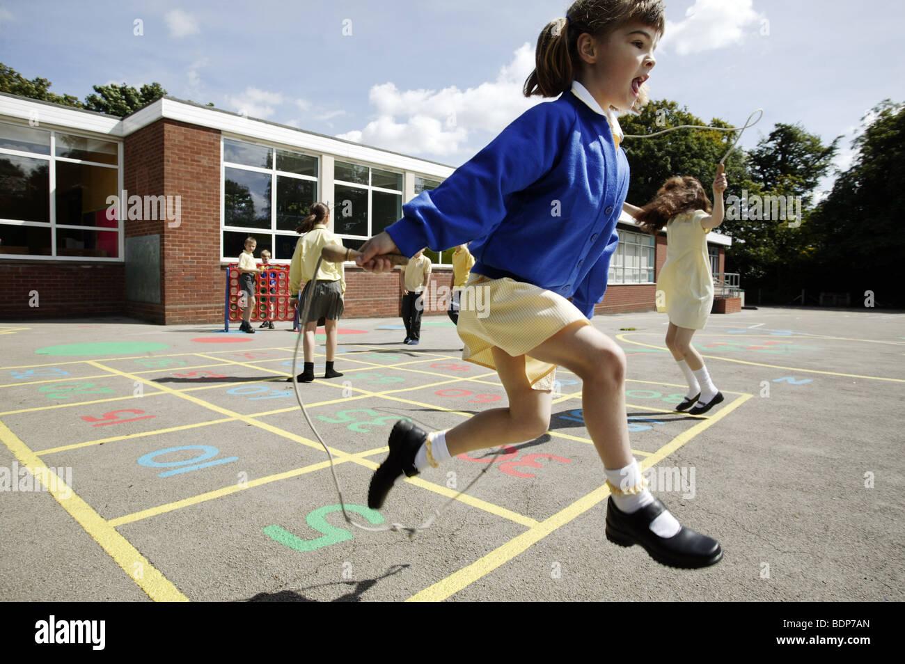 Studentesse saltando in una scuola primaria parco giochi nel Regno Unito. Foto Stock