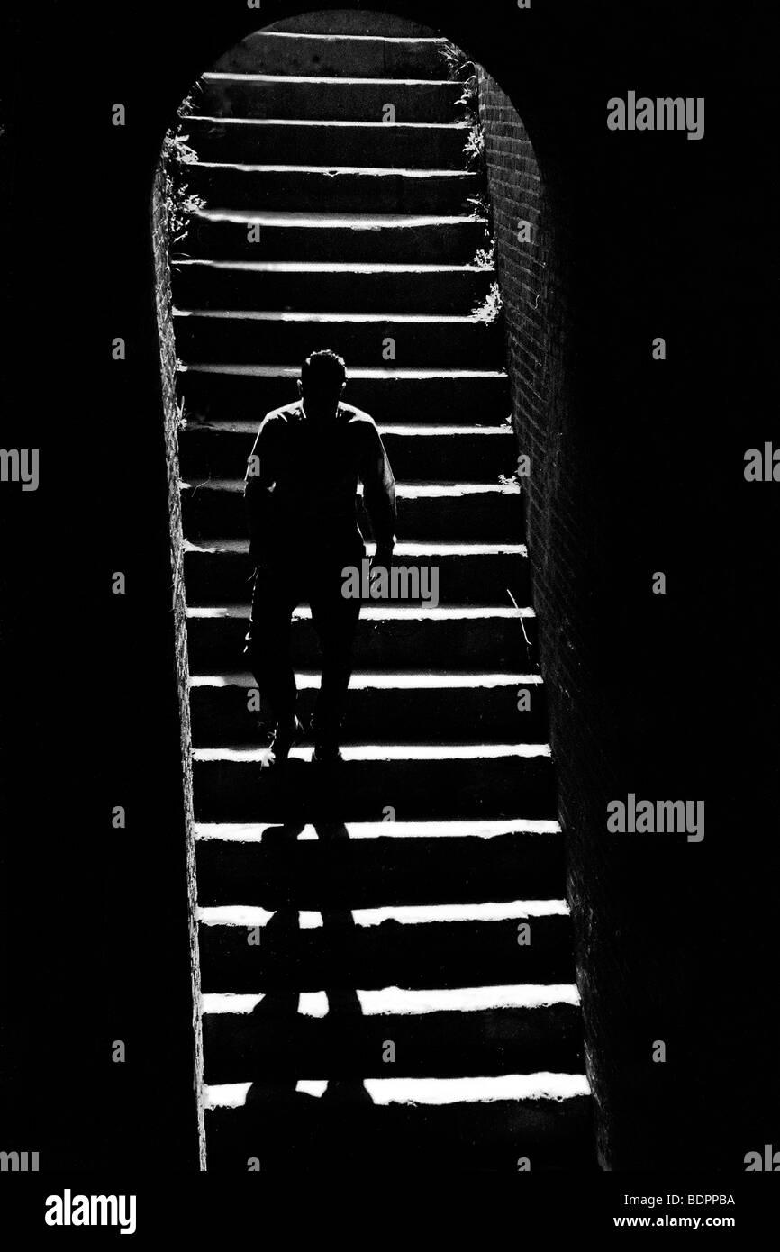 Una figura maschile di discesa delle scale Immagini Stock