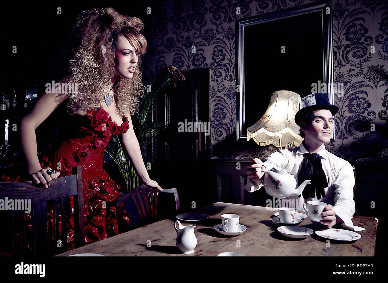 Una giovane donna che indossa un abito rosso guardando un giovane uomo seduto a un tavolo versando una tazza di tè che indossa un cappello a cilindro. Foto Stock