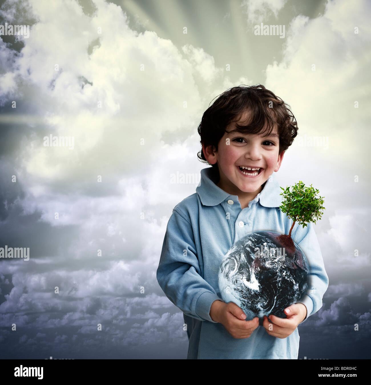 Ragazzo giovane azienda in tutto il mondo con un albero su di esso Immagini Stock