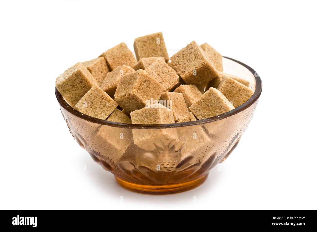 Brown lo zucchero di canna nel recipiente isolato su bianco Immagini Stock