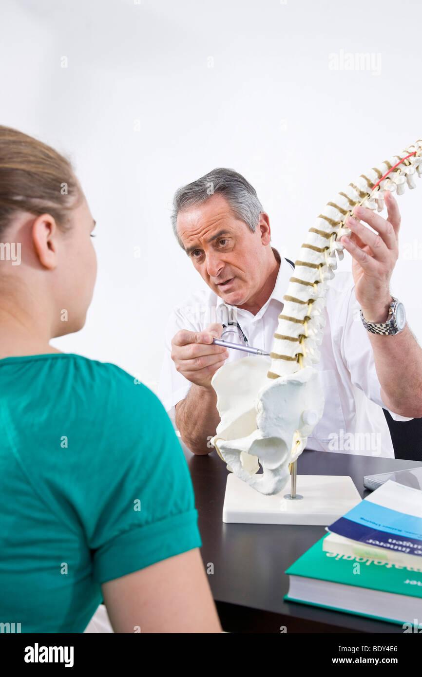 Medico spiegare una colonna vertebrale di un paziente giovane Immagini Stock