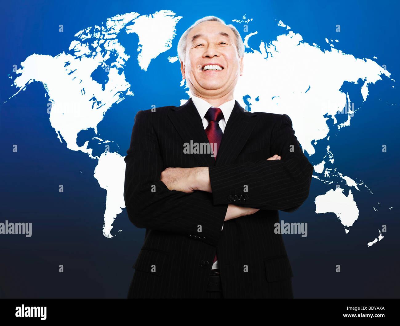 Uomo asiatico a sorridere di fronte mappa del mondo Immagini Stock