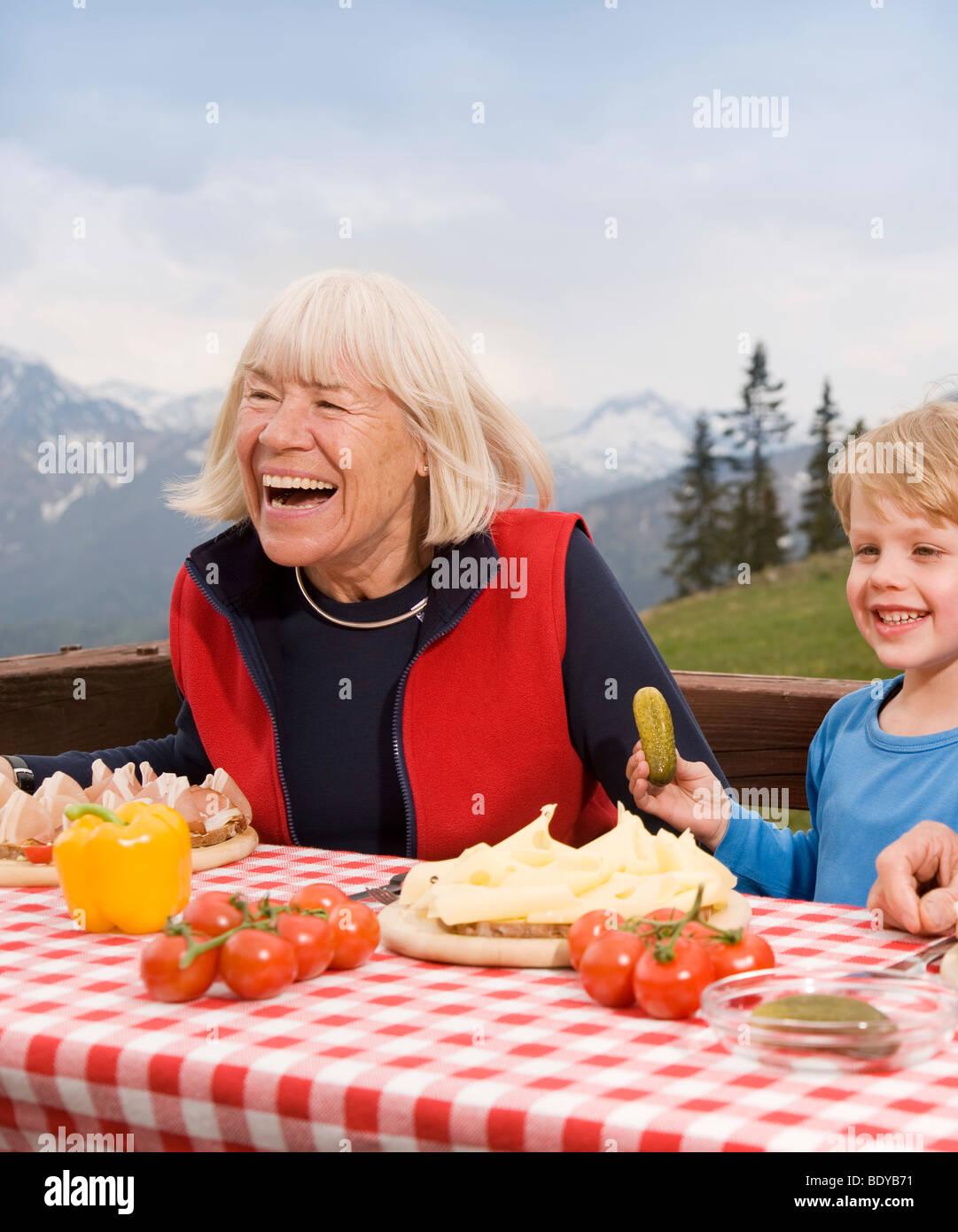 Nonna e nipote di mangiare in montagna Immagini Stock