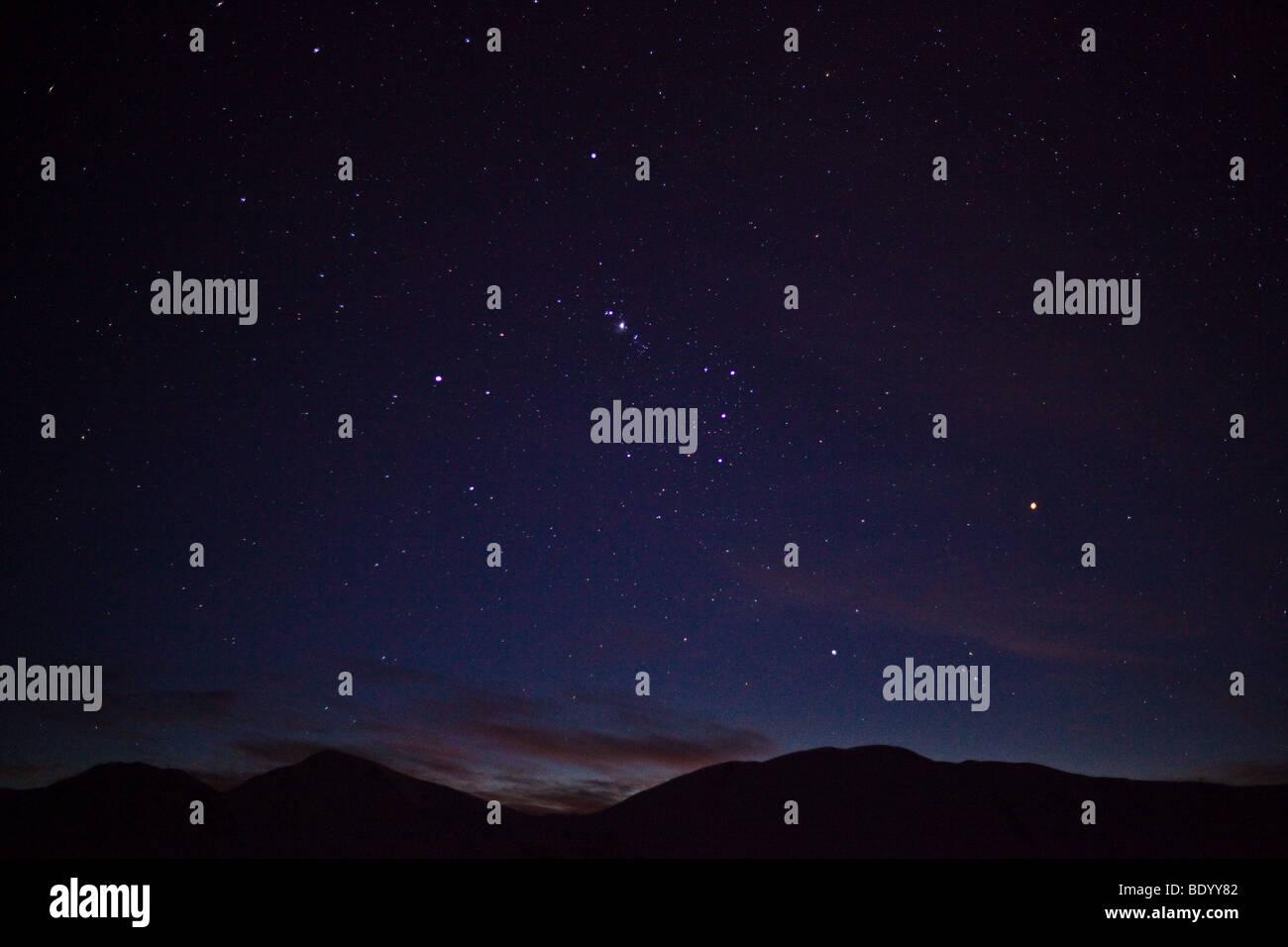 Capovolta la costellazione di Orione impostazione oltre le Alpi del Sud nell'emisfero sud cielo notturno, Isola Immagini Stock