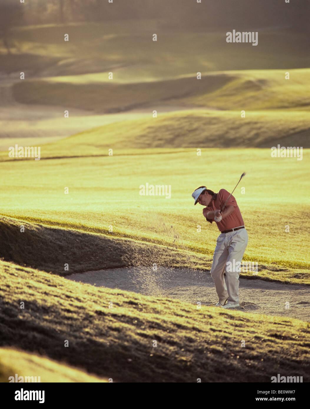 L'uomo golfista scheggiature dalla trappola di sabbia Immagini Stock