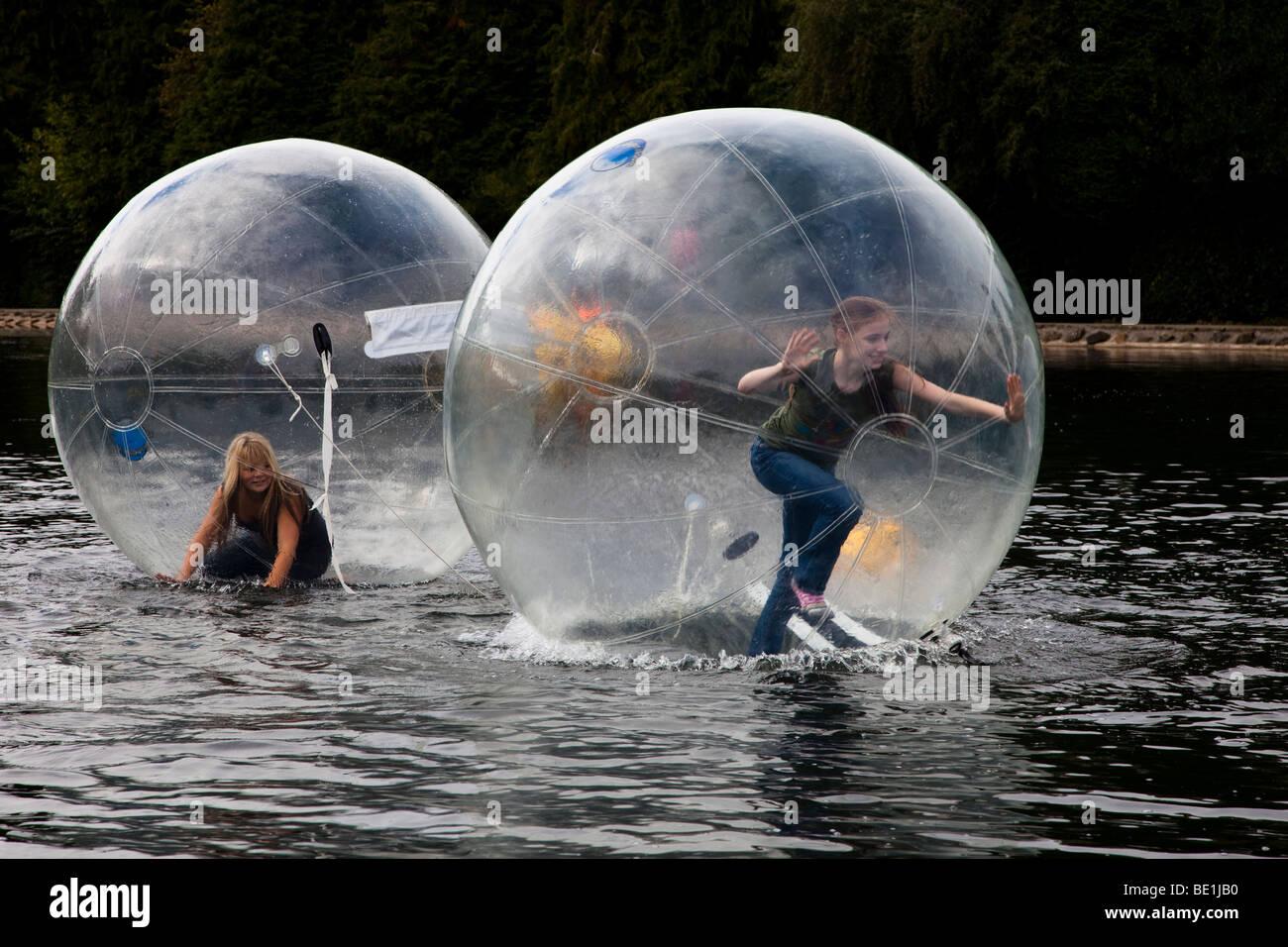 Due giovani ragazze a giocare all'interno di un bubblerunner attraverso il lago di pubblico a Rouken Glen Park, Immagini Stock