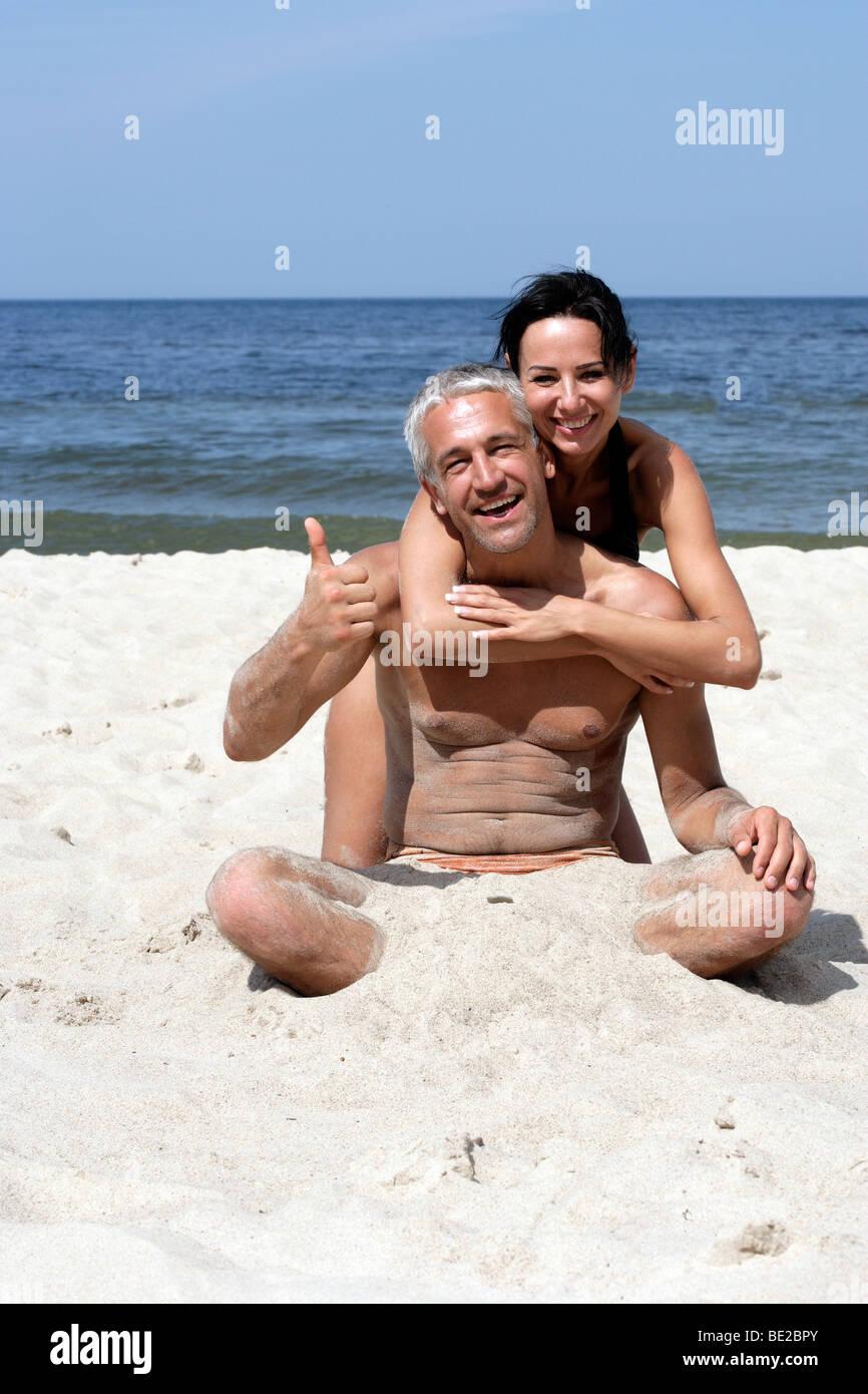 Coppia attraente seduto sulla spiaggia. Uomo bello dando pollice in alto Immagini Stock