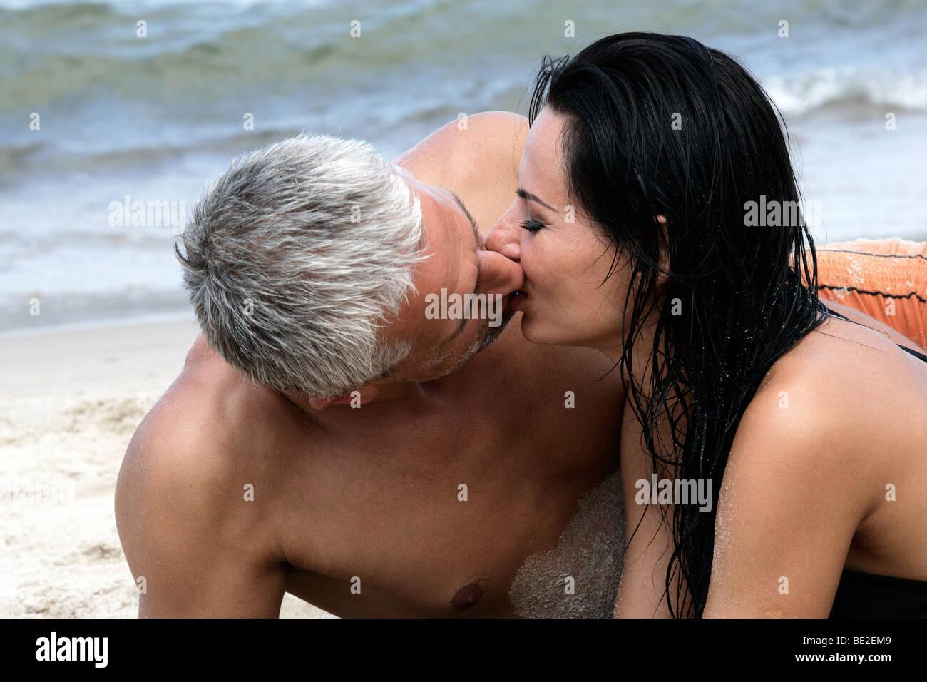 Felice Coppia di mezza età baciare sulla spiaggia, godendo le loro vacanze estive insieme. Foto Stock