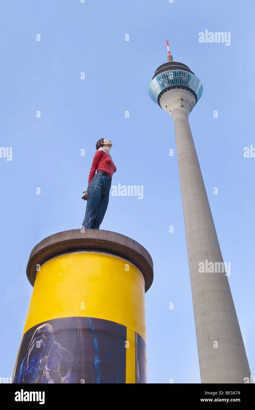 Colonna di pubblicità, la scultura di una donna che guarda verso l'alto, torre Rheinturm nel retro, Duesseldorf, Immagini Stock