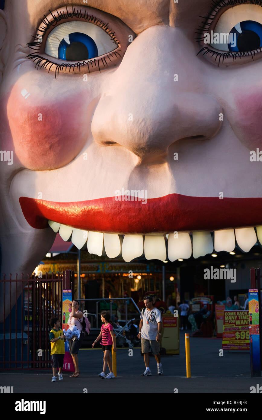 La famiglia presso il volto sorridente entrata del Luna Park. North Shore, Sydney, Nuovo Galles del Sud, Australia Immagini Stock