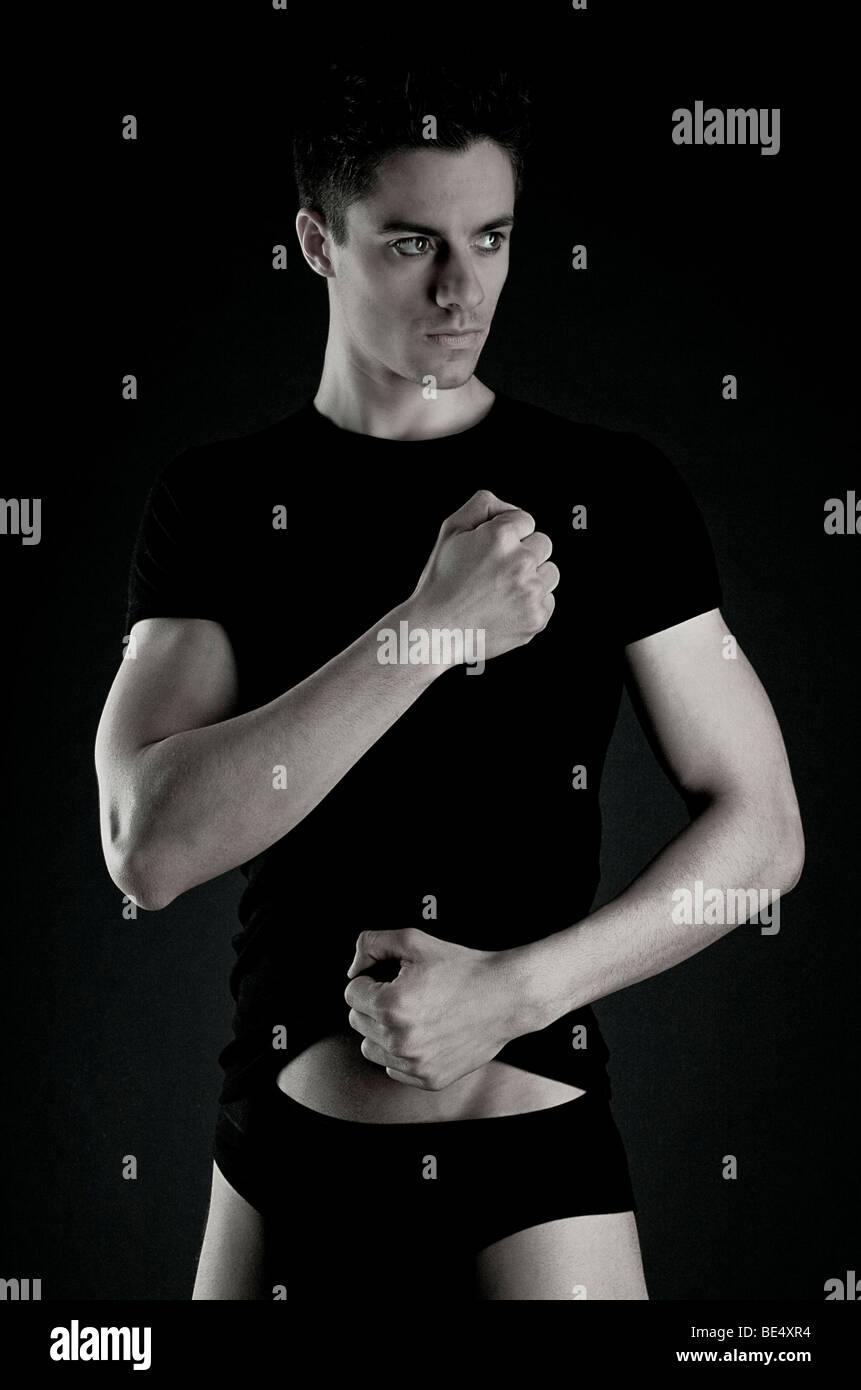Giovane uomo, vestiti di nero, braccia tese, guardando al lato Immagini Stock