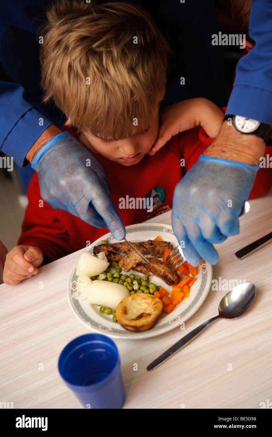 Adulto indossando guanti in lattice blu taglio degli alimenti fino ad un giovane bambino durante la cena di scuola in una scuola primaria, Wales UK Foto Stock