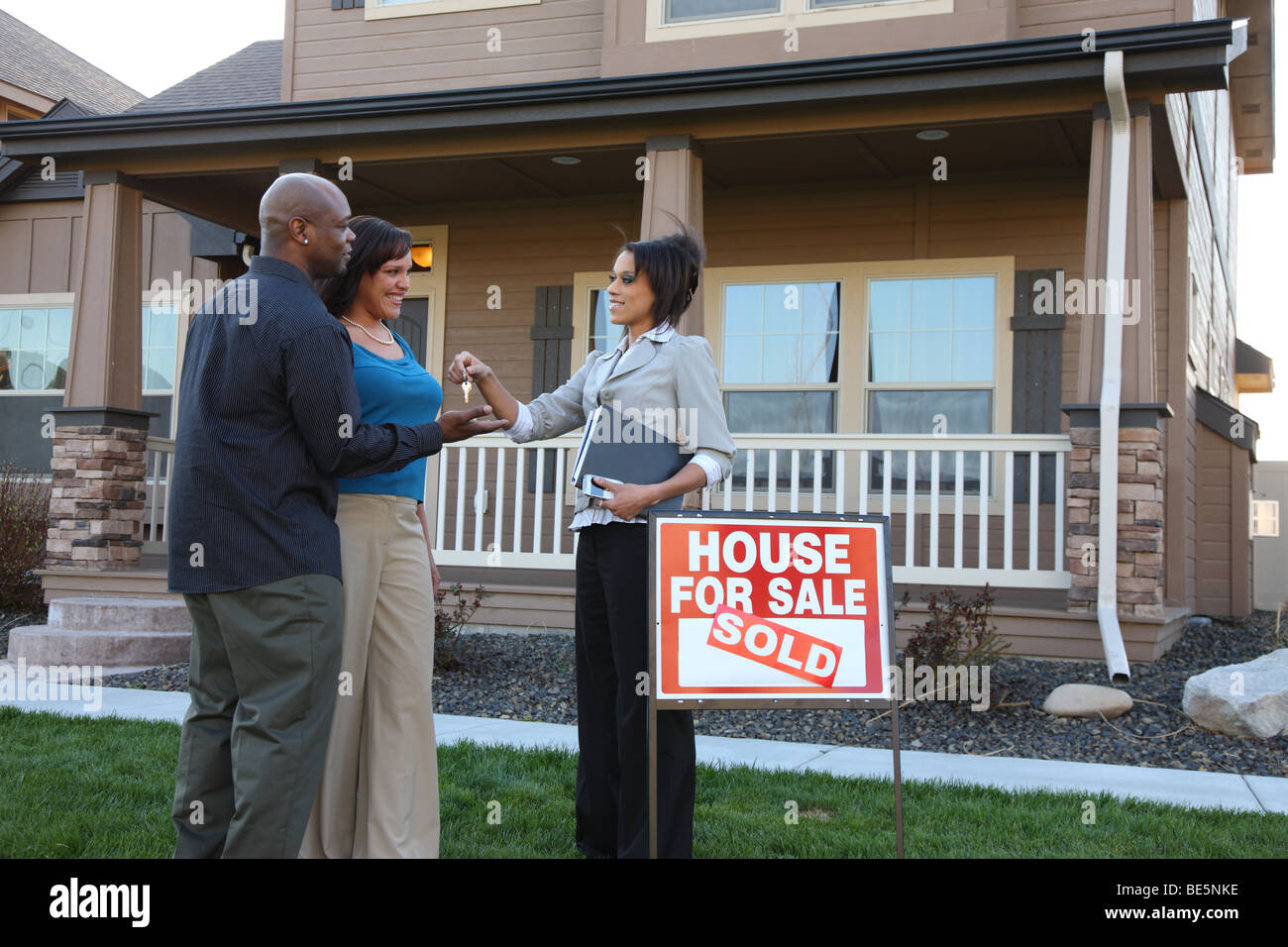 Agente immobiliare dando giovane le chiavi di casa nuova Immagini Stock