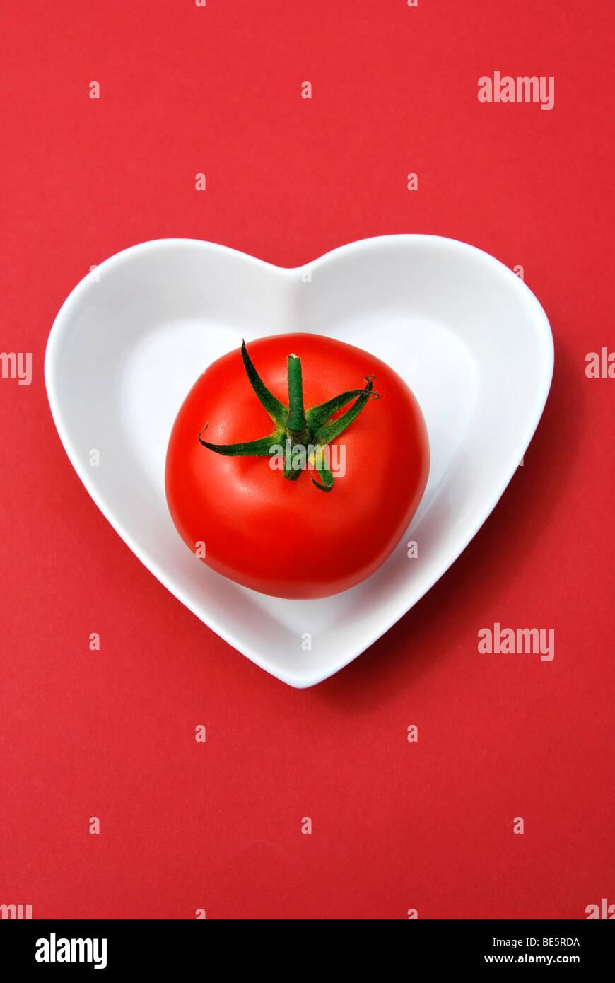 Singola vite il pomodoro in un cuore a forma di tazza di porcellana Immagini Stock