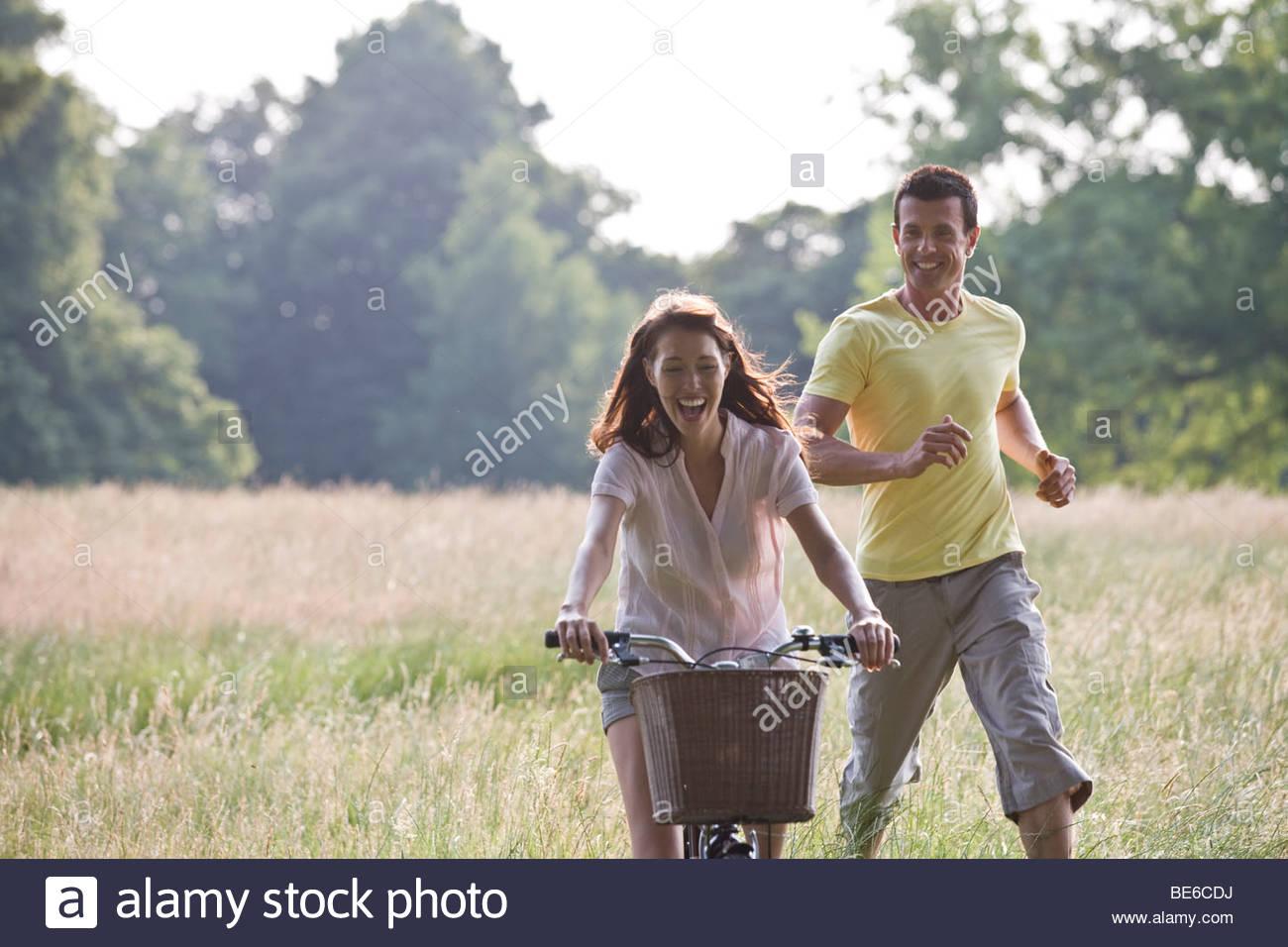Una giovane donna in bicicletta attraverso un campo con il suo fidanzato in esecuzione dopo il suo Immagini Stock
