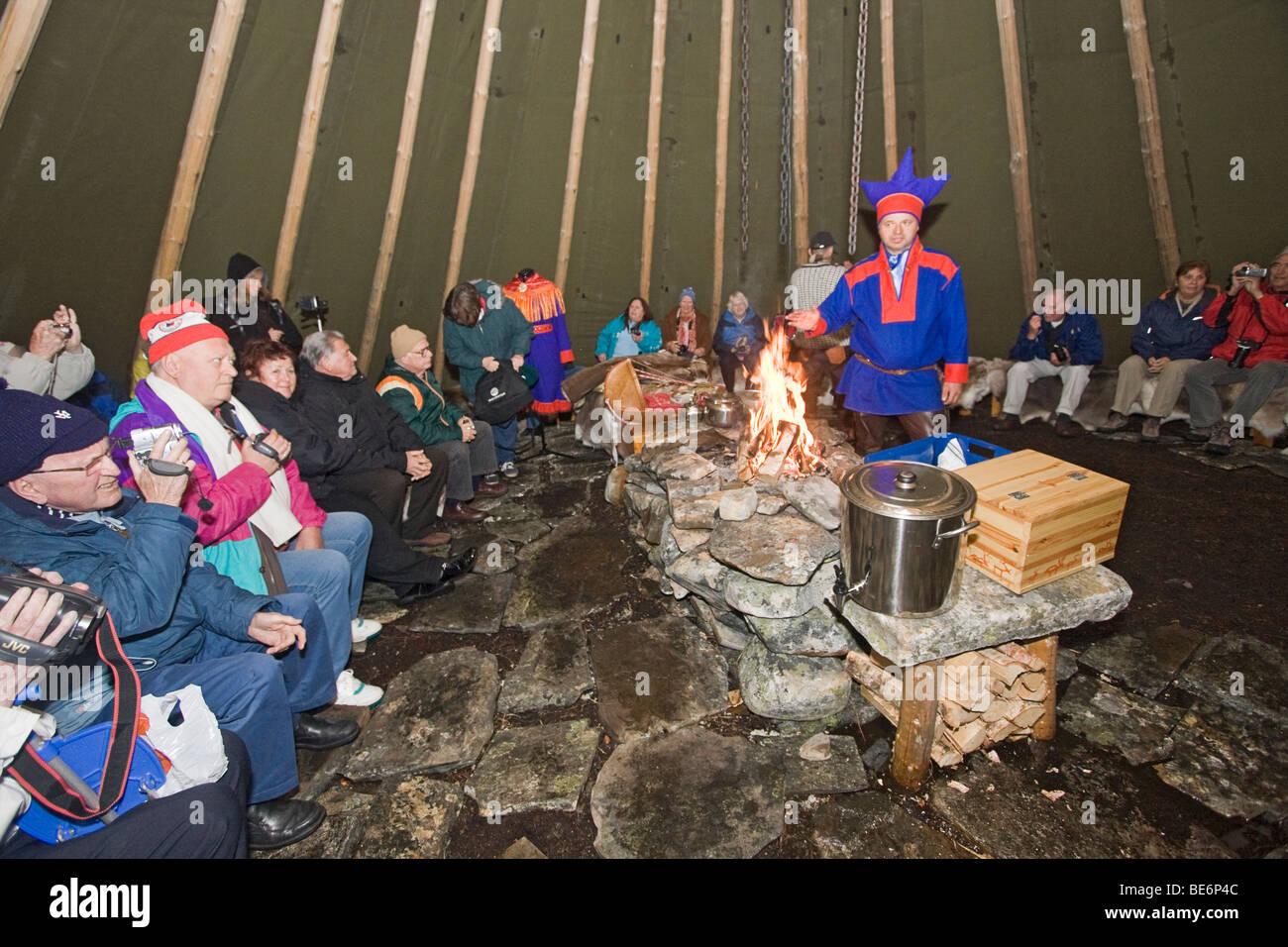 Sami uomo in abbigliamento tradizionale parla di vita quotidiana in una versione più grande della tenda che Immagini Stock