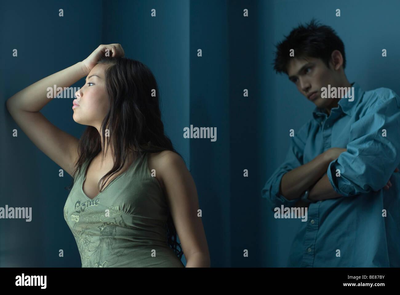 Giovane donna tenendo la testa e lo sguardo lontano, impaziente uomo in piedi dietro di lei con le braccia incrociate Foto Stock