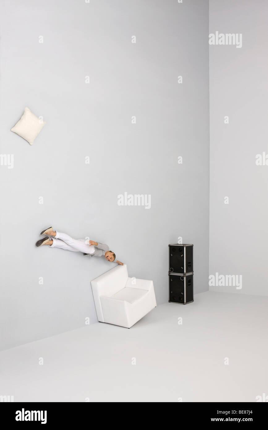 Donna midair flottante, tenendo sulla poltrona, essere soffiata via dal suono emesso dagli altoparlanti Immagini Stock