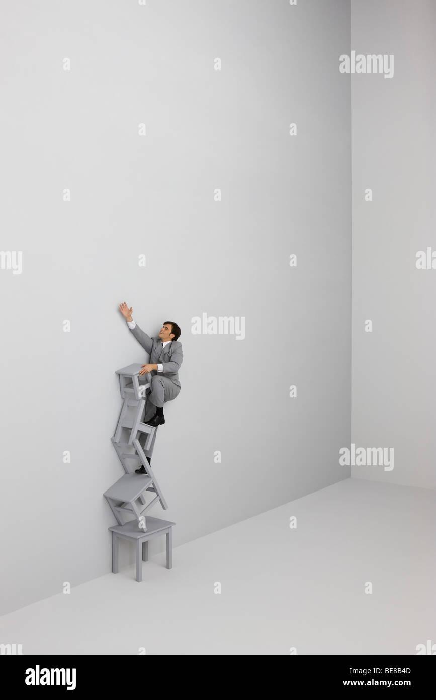 Imprenditore arrampicata e raggiungere la cima della scala fatta di sedie impilate Immagini Stock