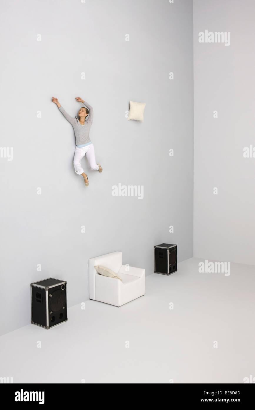 Donna con le braccia sollevate midair galleggianti al di sopra di poltrona Immagini Stock