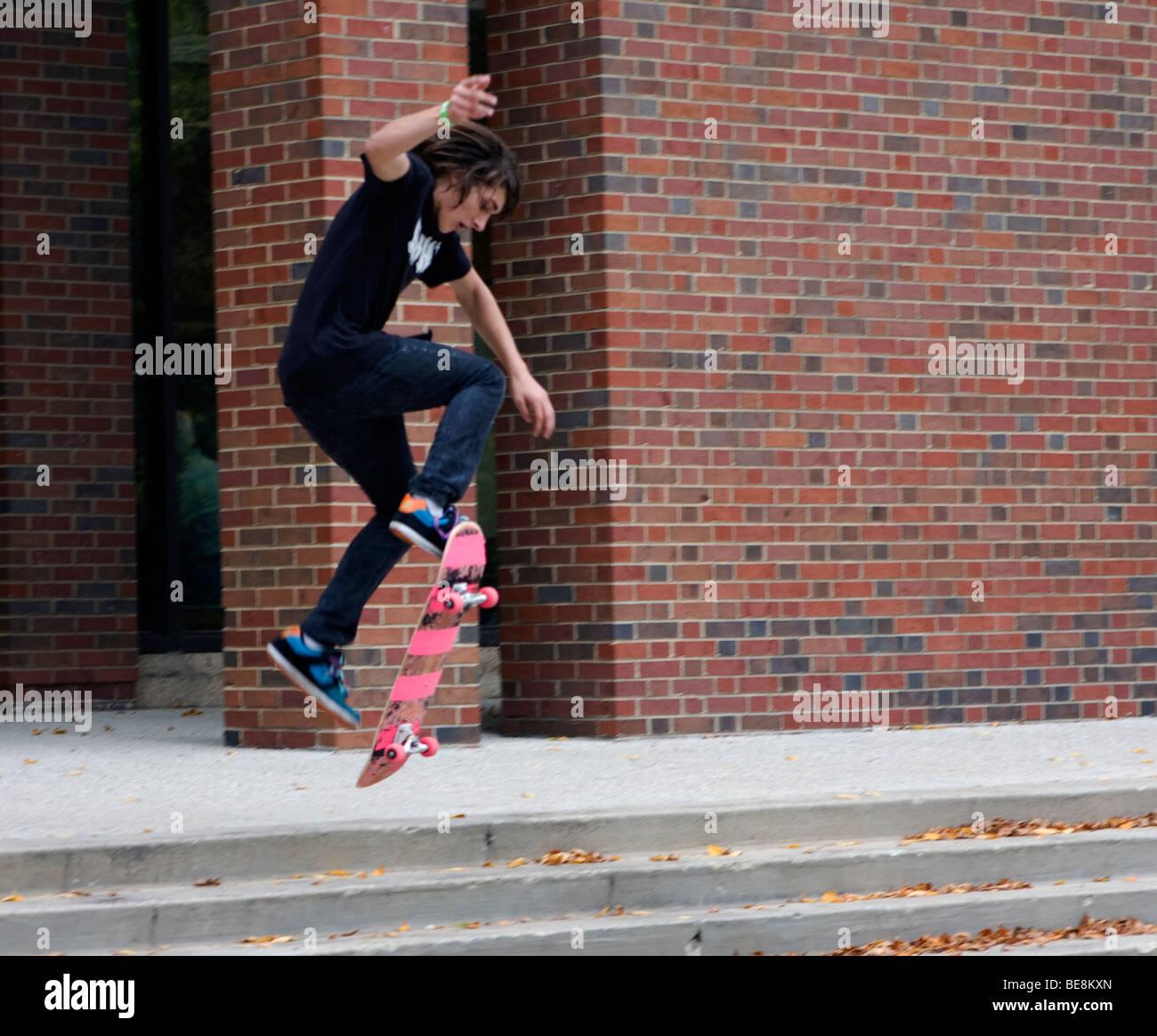 Un giovane uomo di pratiche il suo skateboard trucchi sui passi ad una biblioteca universitaria a Milwaukee, Wisconsin, Immagini Stock
