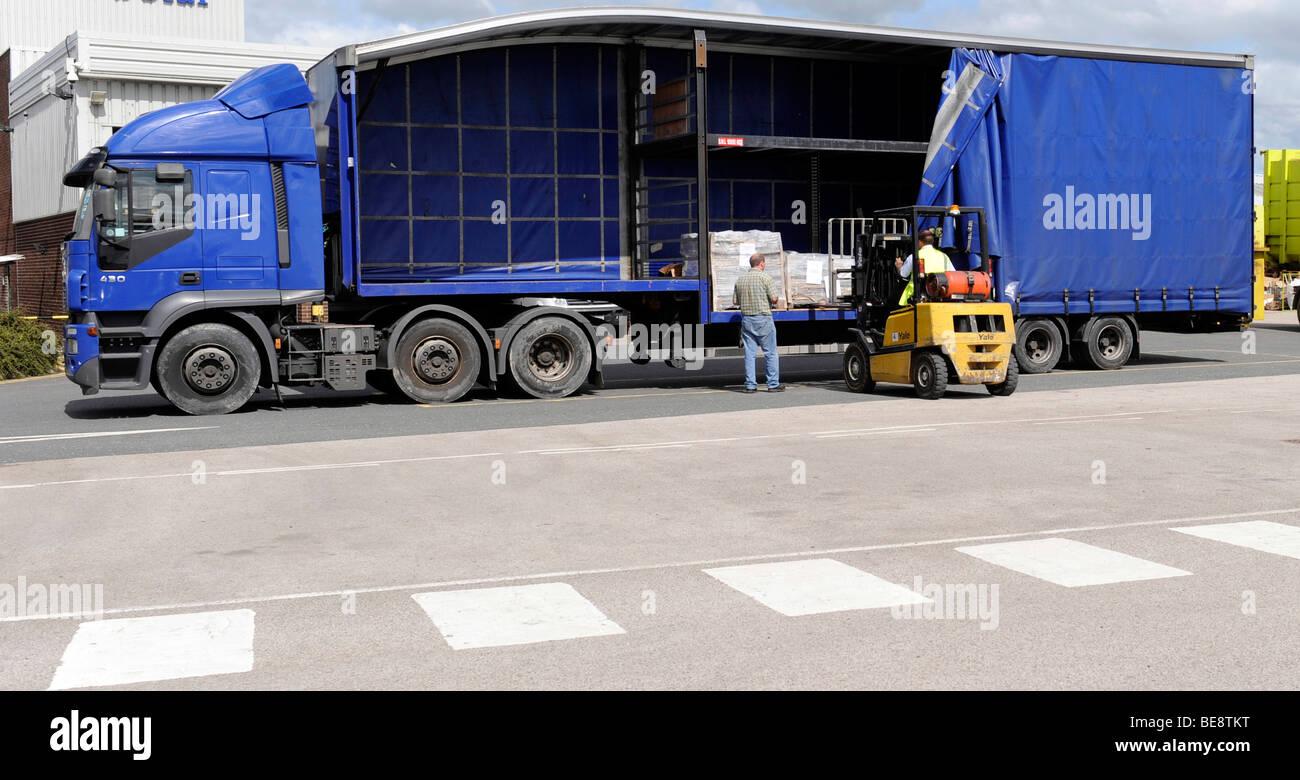 Un carrello elevatore a forche carica scarica un double deck curtainsided rimorchio e carrello Immagini Stock