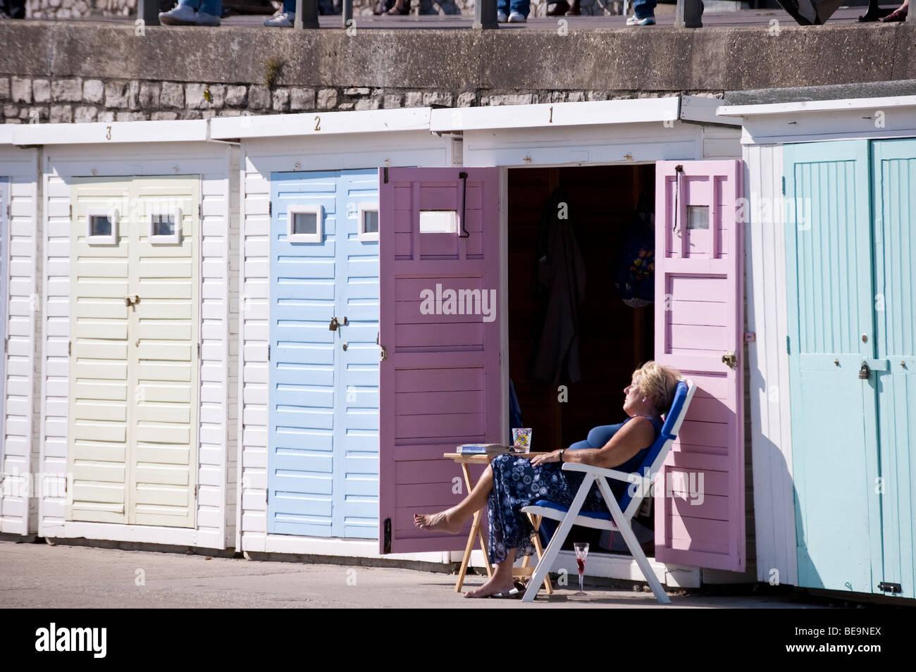 Donne di mezza età a prendere il sole sulle sdraio da aprire porte di Beach Hut con libro e bicchiere di vino Immagini Stock