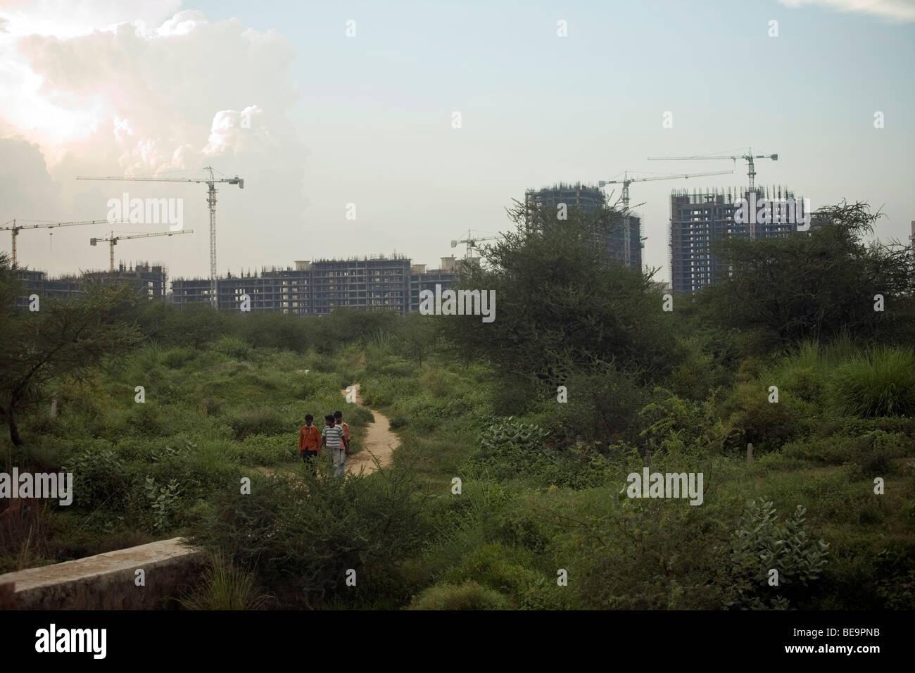 I lavoratori di ritorno dal sito di costruzione di un nuovo sviluppo a Gurgaon, India Immagini Stock