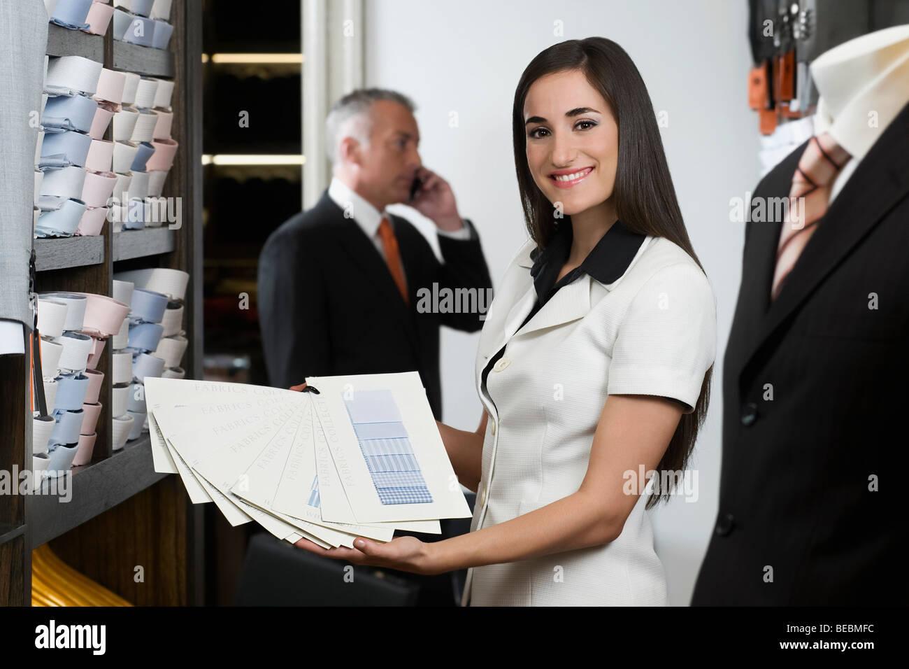 Addetto alle vendite tenendo i campioni di tessuto in un negozio di  abbigliamento Immagini Stock 0760d5f89a0