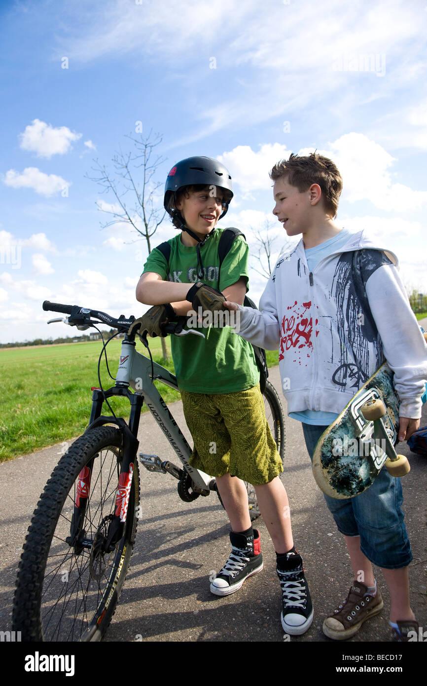Un ragazzo con uno skateboard e un ragazzo su una mountain bike in campagna Immagini Stock