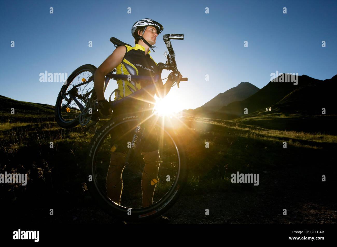 Mountainbiker portando la sua bici, Tirolo del nord, Austria, Europa Immagini Stock