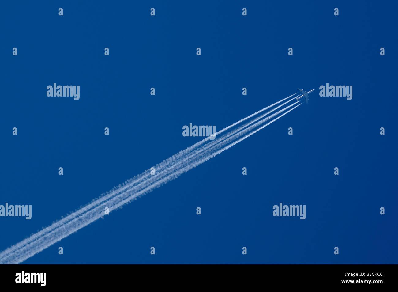 Quattro-motore aereo di linea il disegno di una contrail in un cielo blu chiaro Immagini Stock