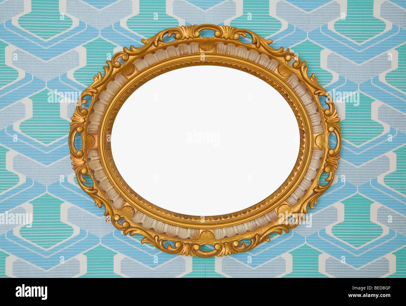 Kitschy golden plastica cornice ovale, orizzontale montato su carta da parati a partire dagli anni Sessanta o Settanta, Immagini Stock