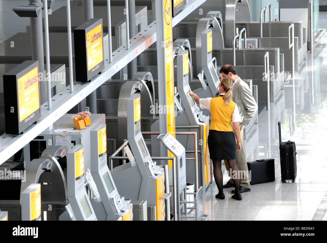 Lufthansa dipendente spiegando a un passeggero la Quick-Check-in-terminale della Lufthansa, il Terminal 2 dell'aeroporto Foto Stock